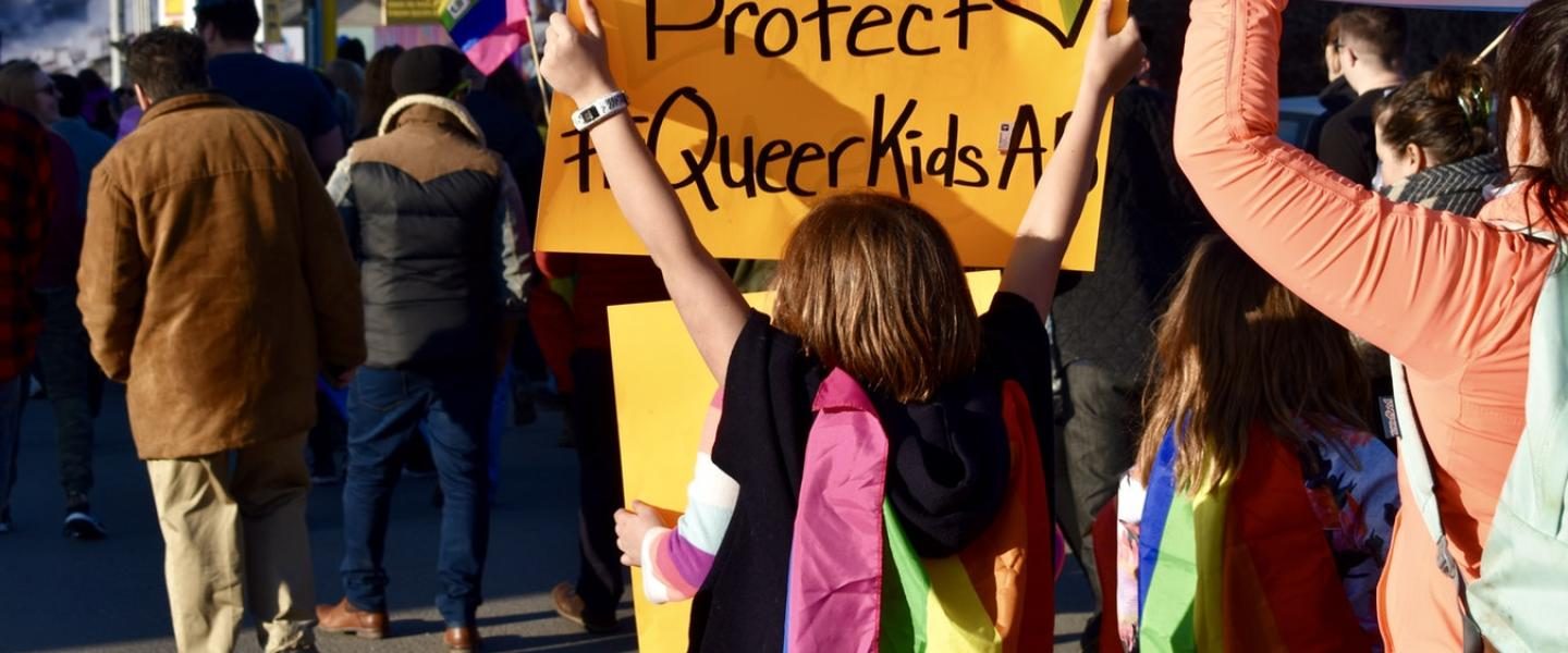 "group of people holding a ""Defend & Protect queer kids"" sign"